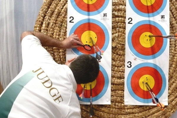 A Scottish Archery judge assessing the scoring value of an arrow